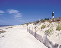 Photo of a beach with scenis lighthouse in the distance
